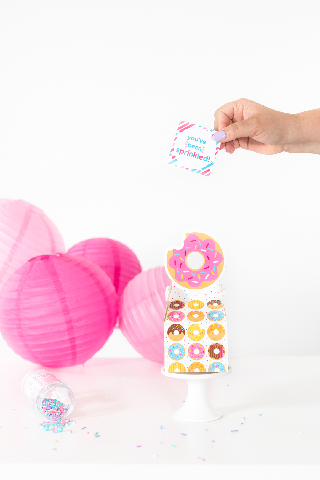 adding cute sprinkle gift tag to donut gift box