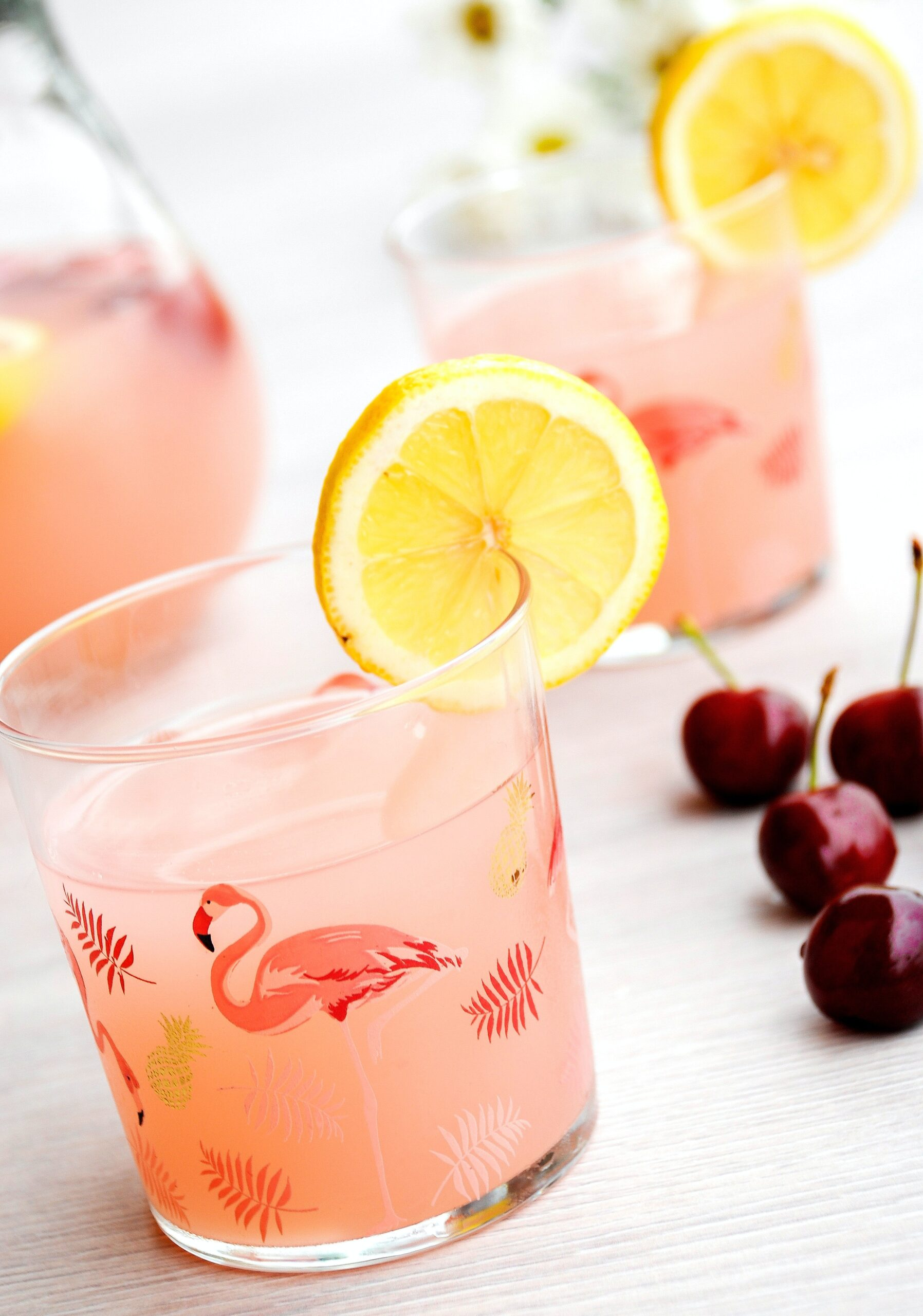 flamingo glasses filled with pink beverage and lemon wedge
