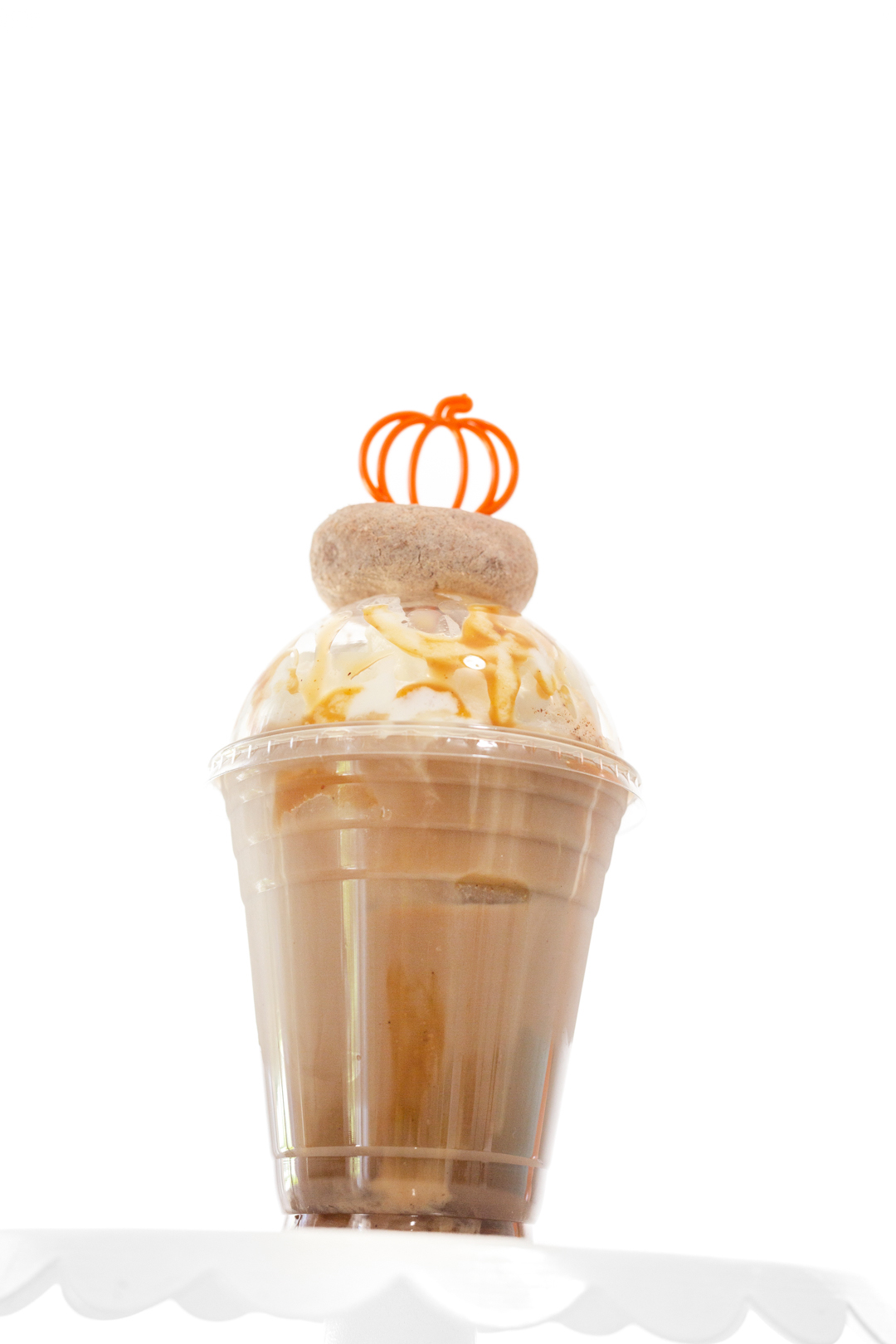 fancy pumpkin iced coffee with mini donut on top and pumpkin stirrer
