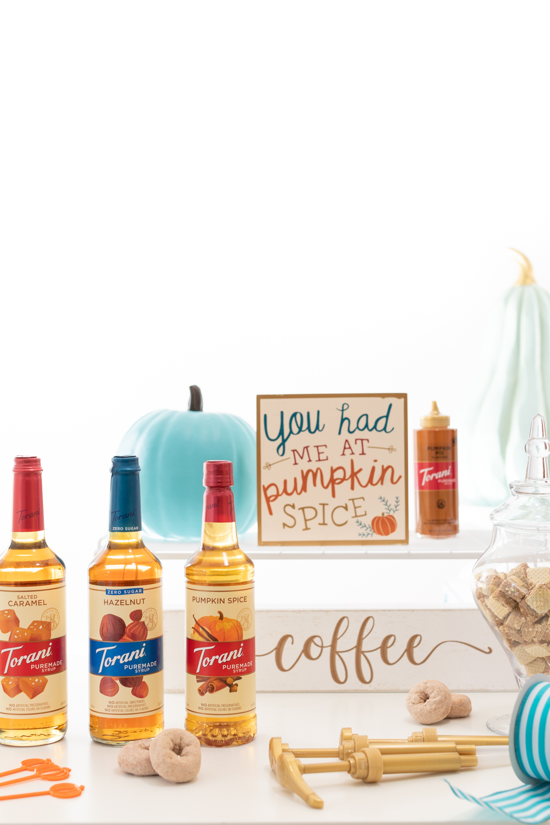 gathering everything needed to put together a pumpkin spice coffee bar from syrups to props and signs