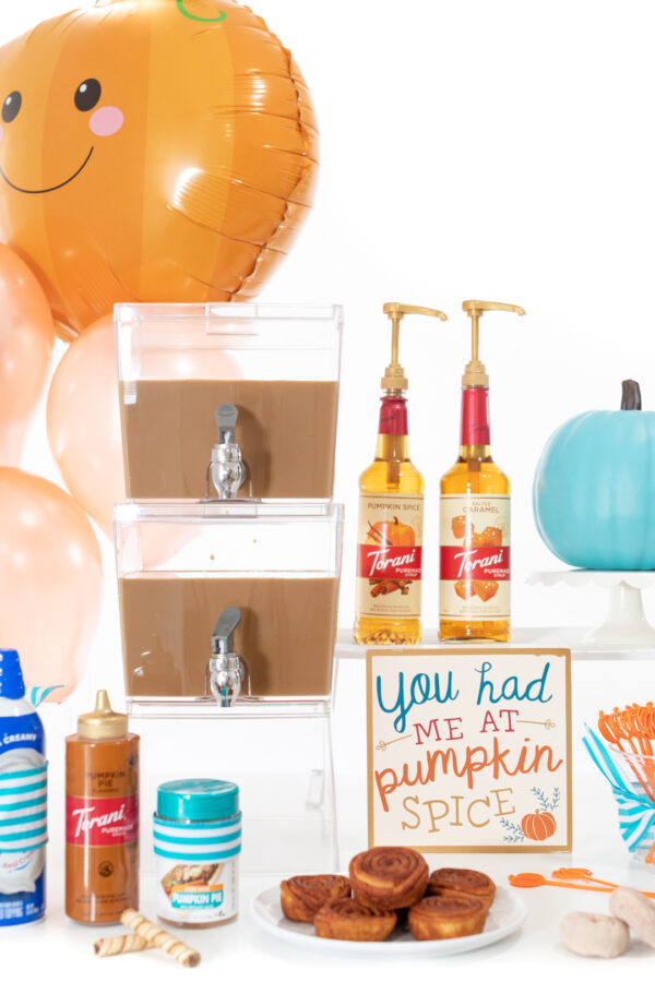 iced coffee bar with double beverage dispenser, pumpkin spice sign, torani fall inspired syrups, sauces and more.