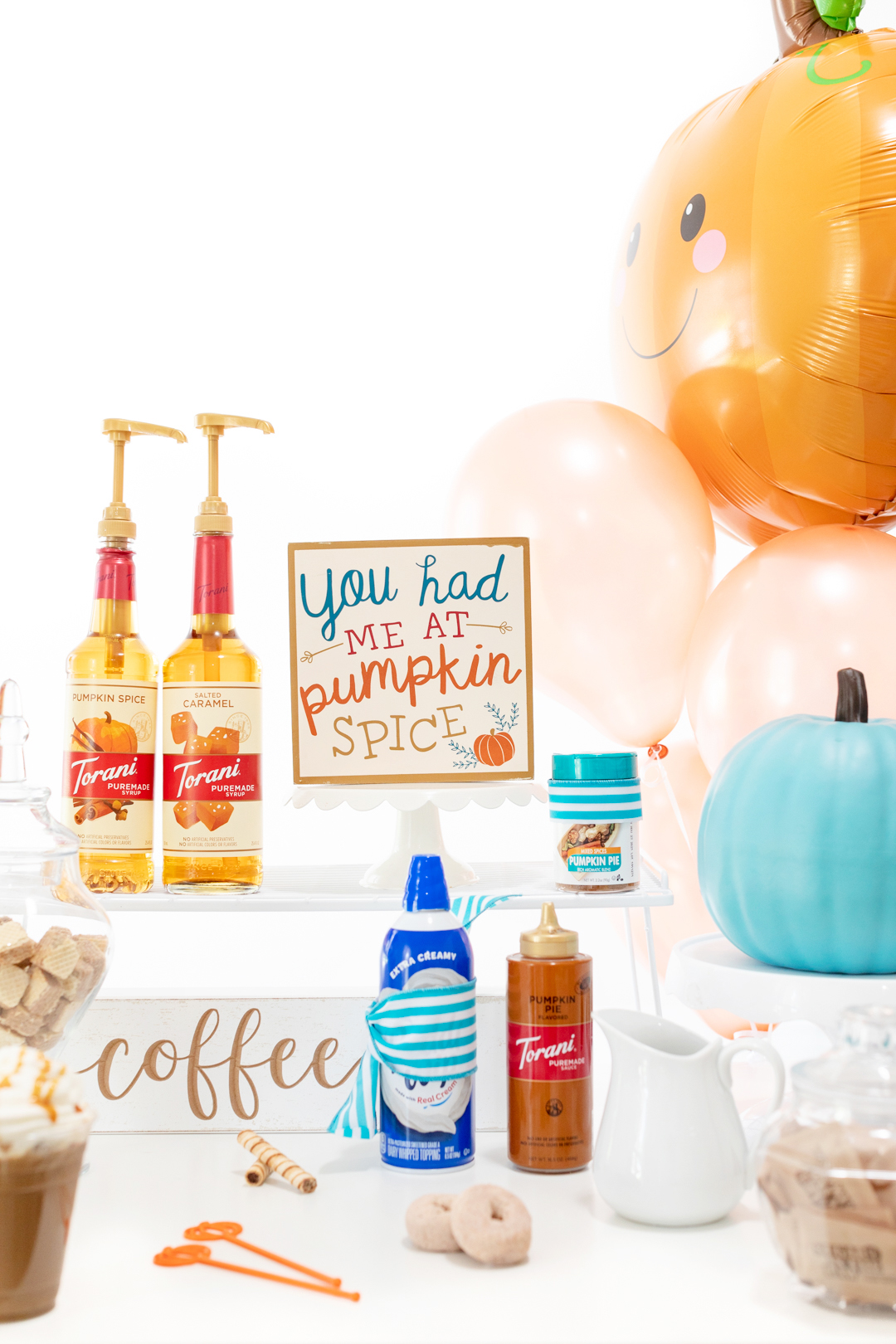 pretty iced coffee bar with syrups, signs, whipped cream, sauces and balloons to decorate.