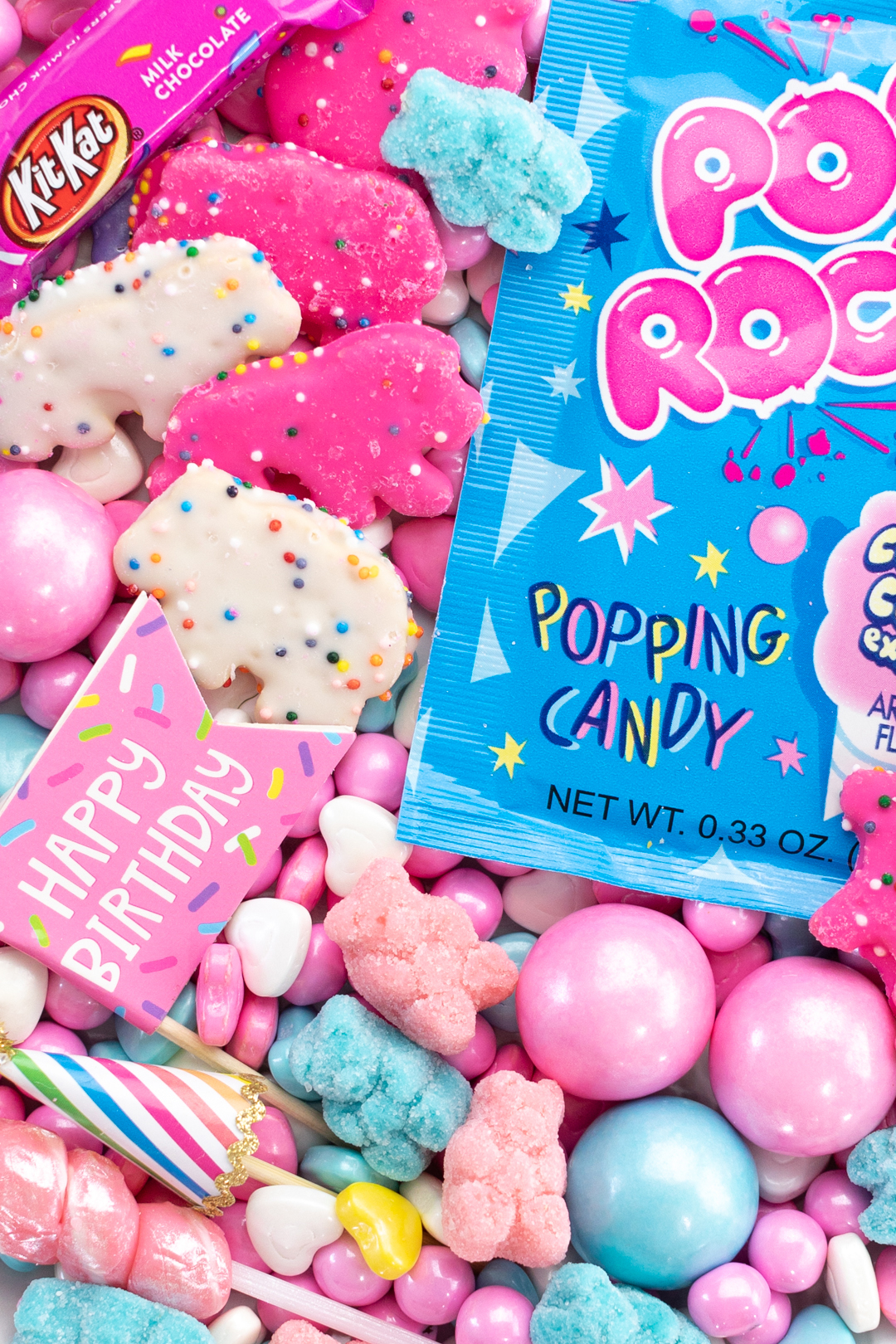 up close view on a small candy board with pink and white circus cookies, pastel gummy bears, pastel gumballs and bubble gum pop rock candy