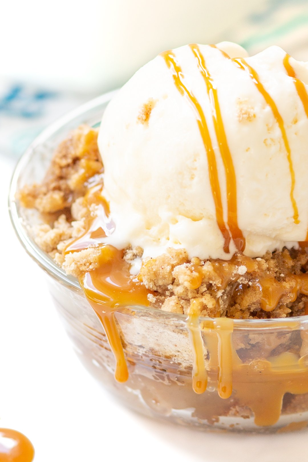 bowl of apple dump cake with oozing caramel and melty ice cream on top.