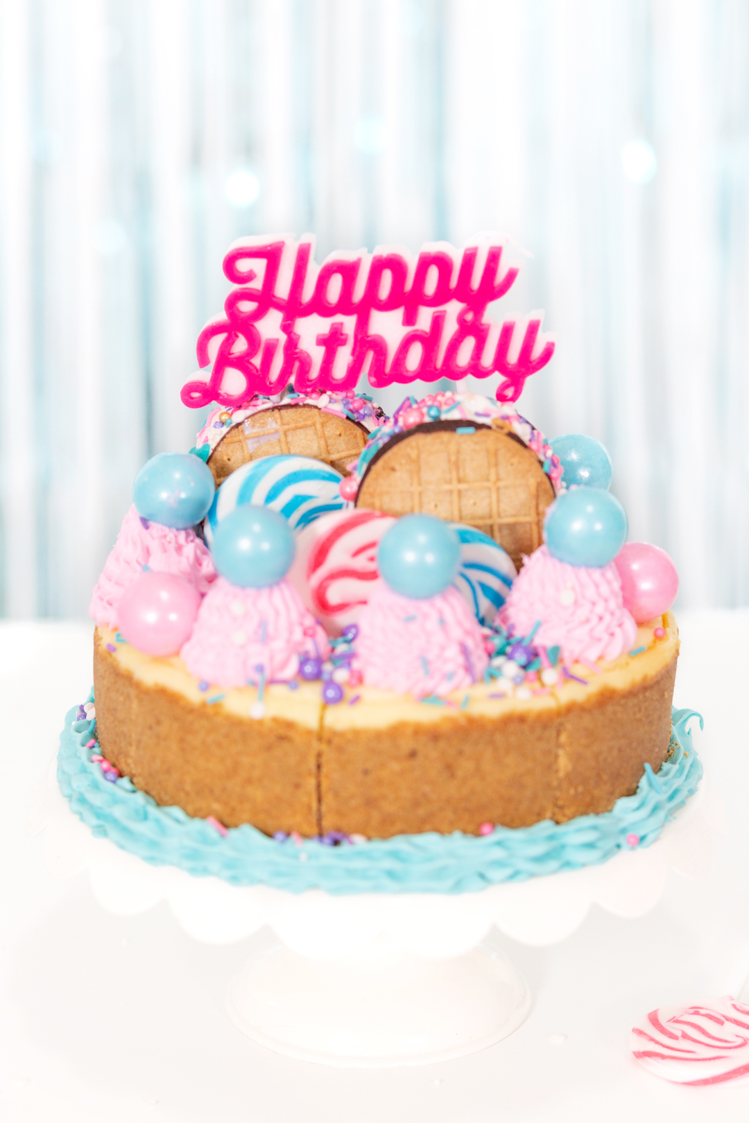 birthday cheesecake up close with pink and blue cake decorations