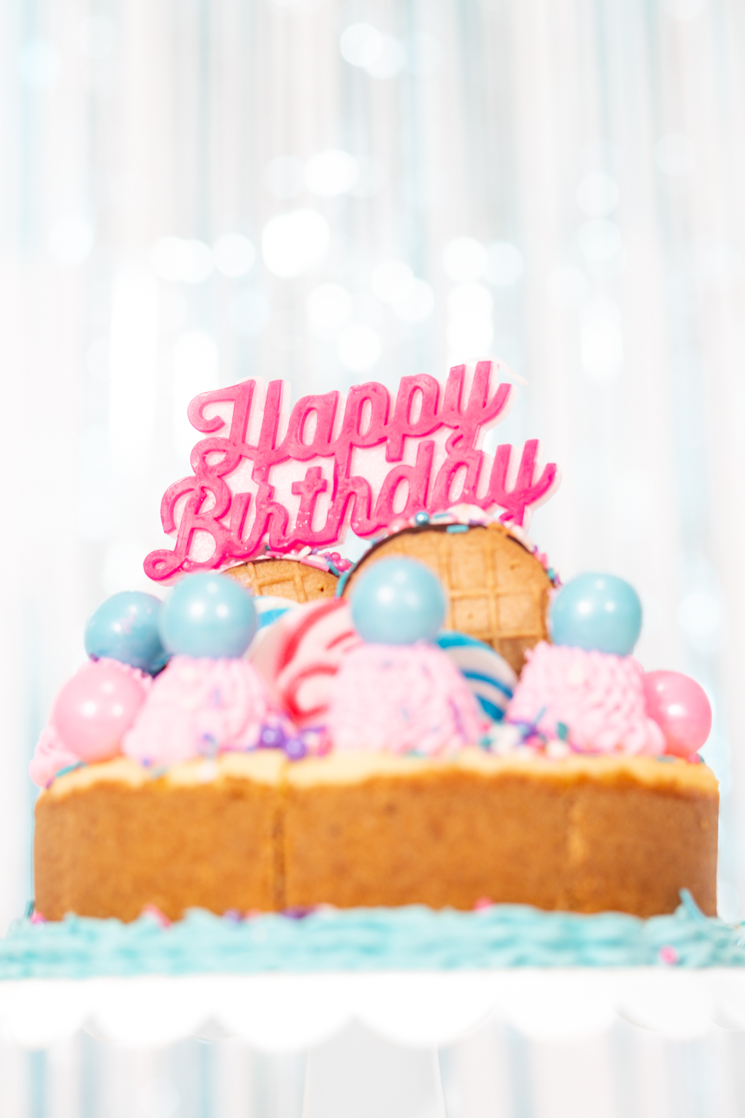 pretty birthday cheesecake with pink and blue cake toppings from lollipops to gumballs