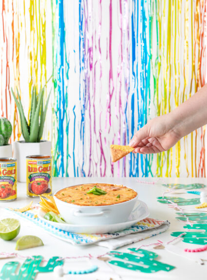 dipping a tortilla into mexican dip in party setting