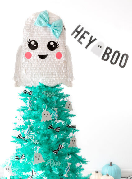 ghost themed halloween christmas tree with banner that says hey boo.