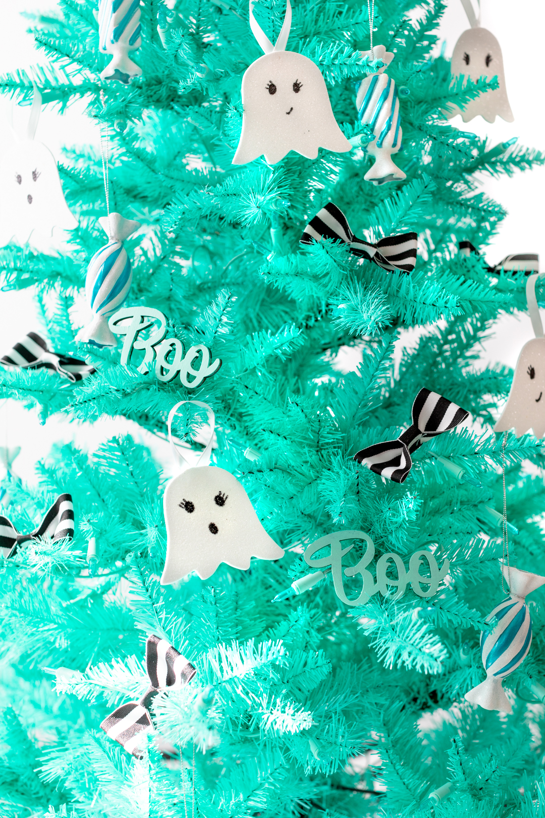 close up of a halloween christmas tree with black and white striped bow decorations, ghost ornaments and candy ornaments