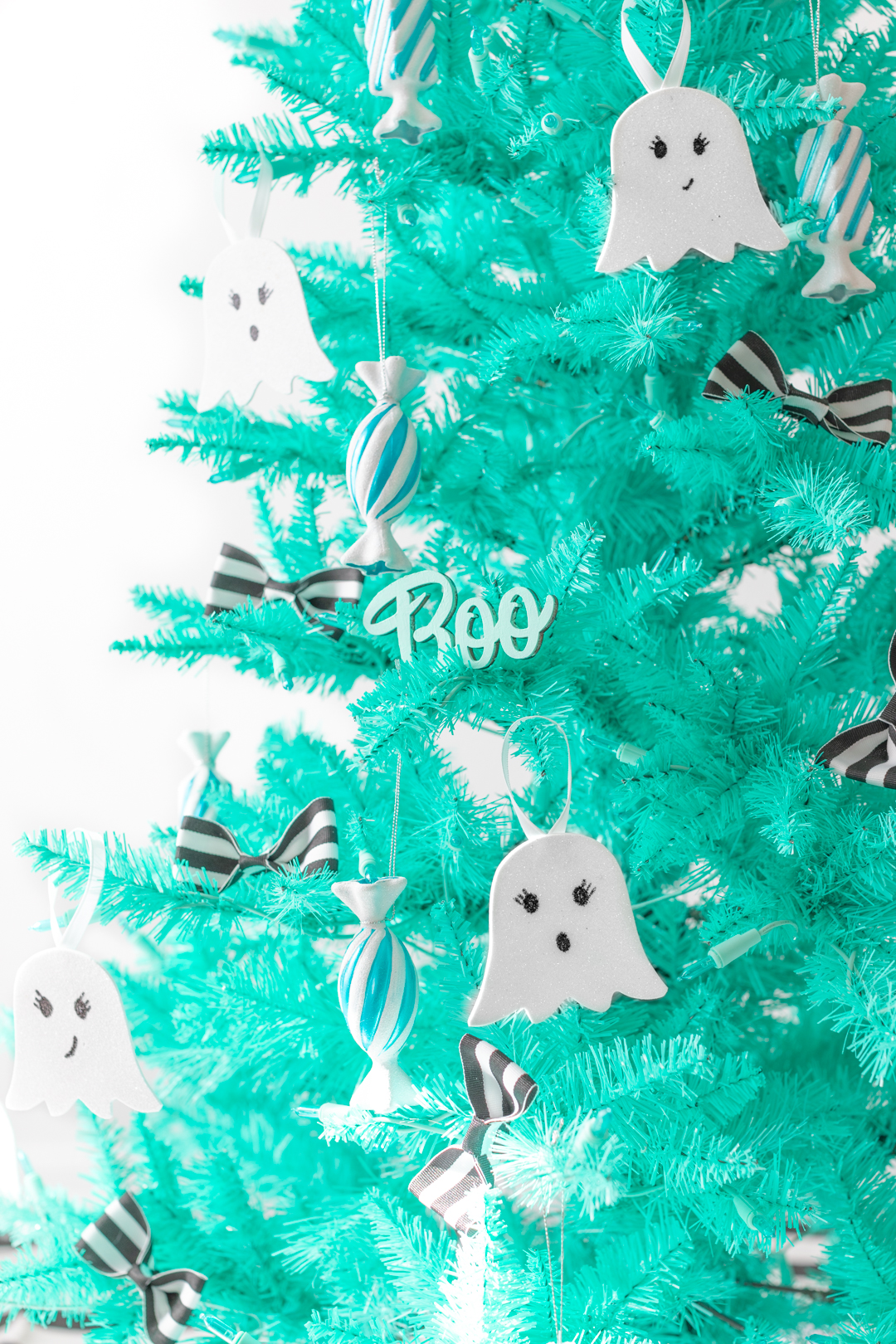 teal christmas tree decorated for halloween with ghost ornaments and candy ornaments