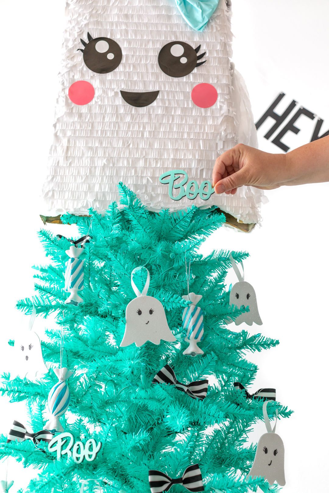 cute hand-painted boo sign being used as a christmas tree decoration for halloween
