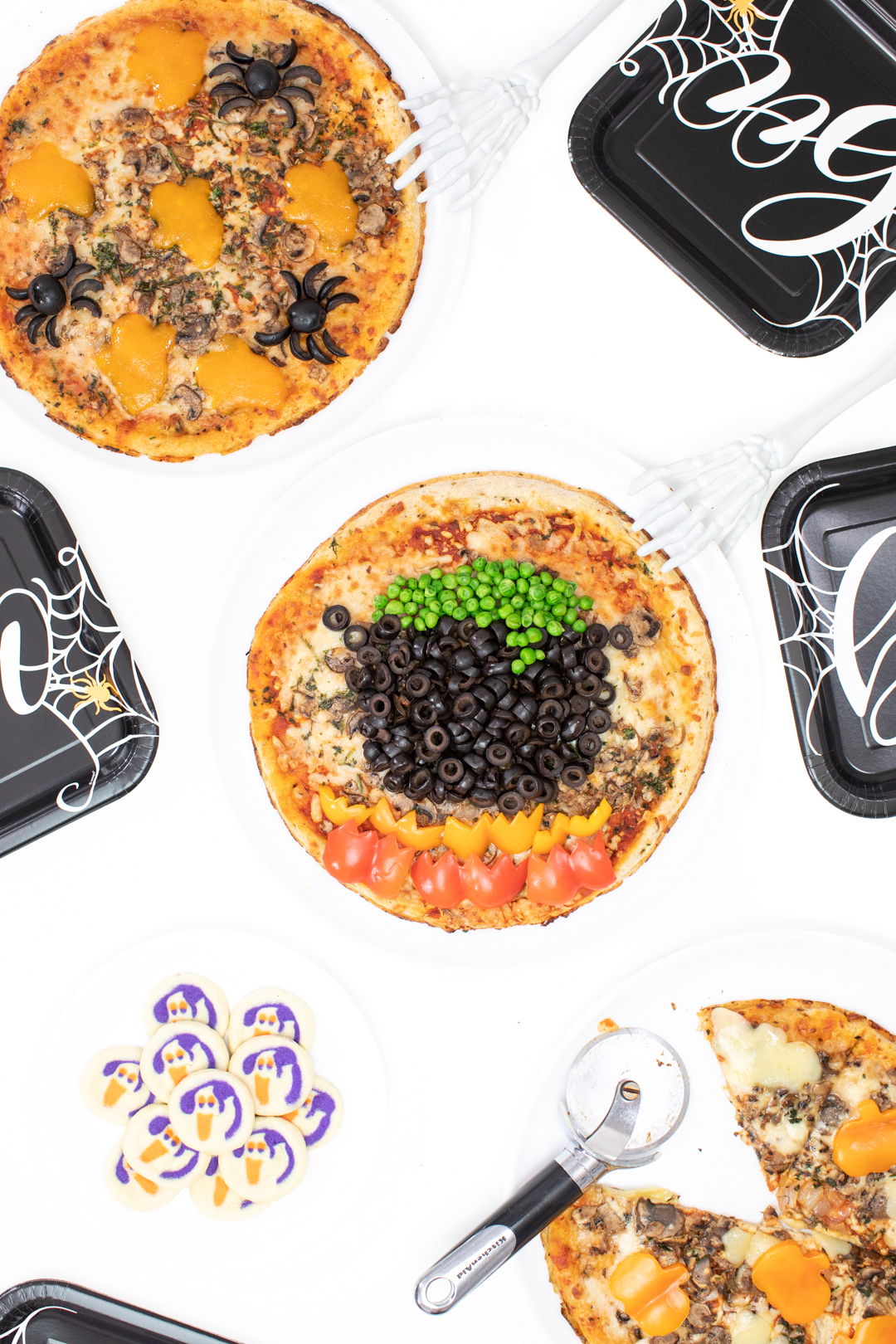 witch cauldron pizza and ghost cookies set out on a table for serving