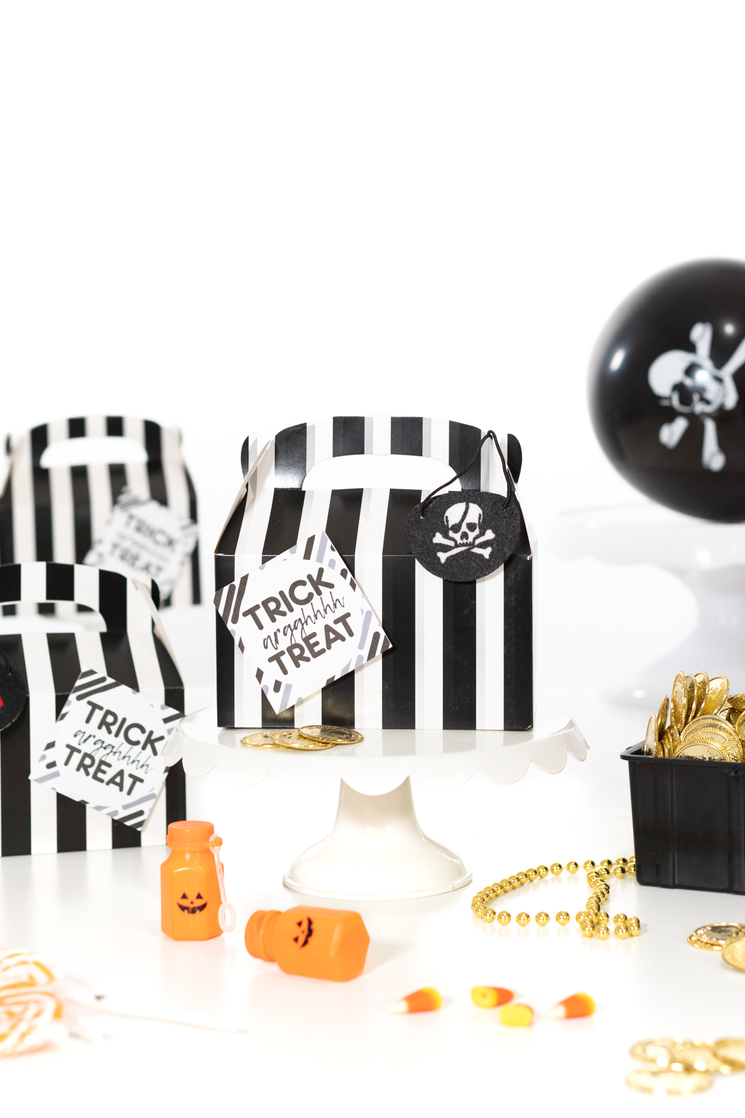 pirate favor boxes, black and white striped with gift tag on them that says trick arrgghh treat on it. Cute for Halloween door drops.