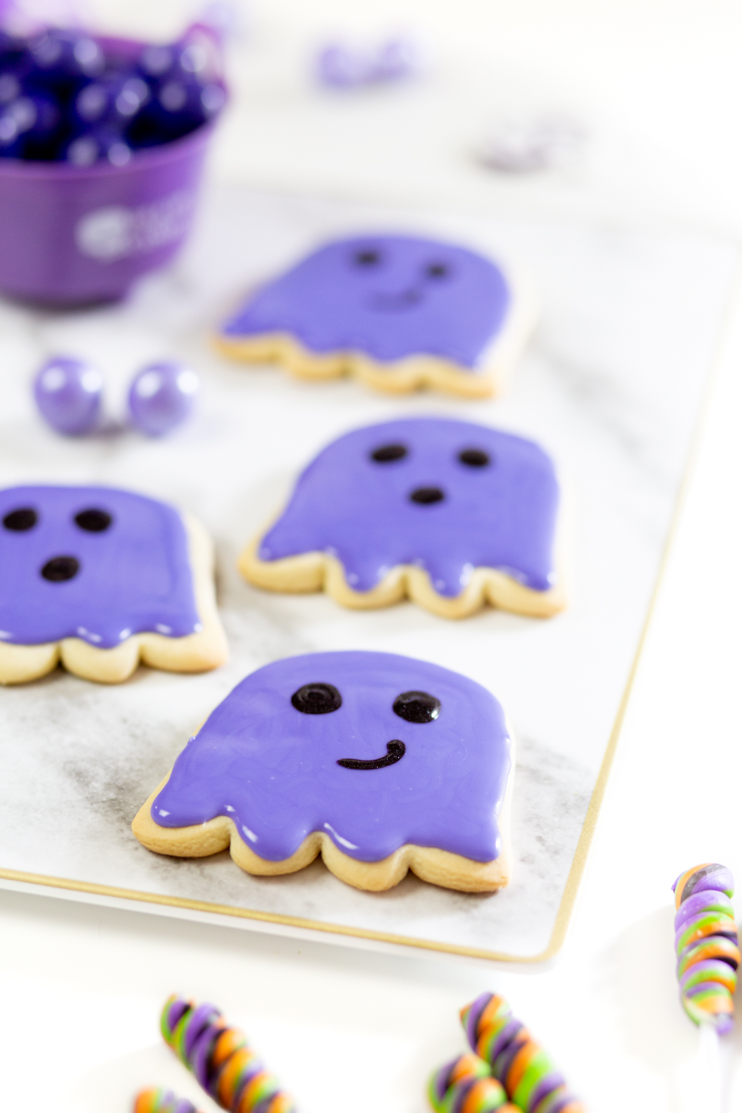 purple ghost cookies on a tray, freshy iced with purple cookie icing