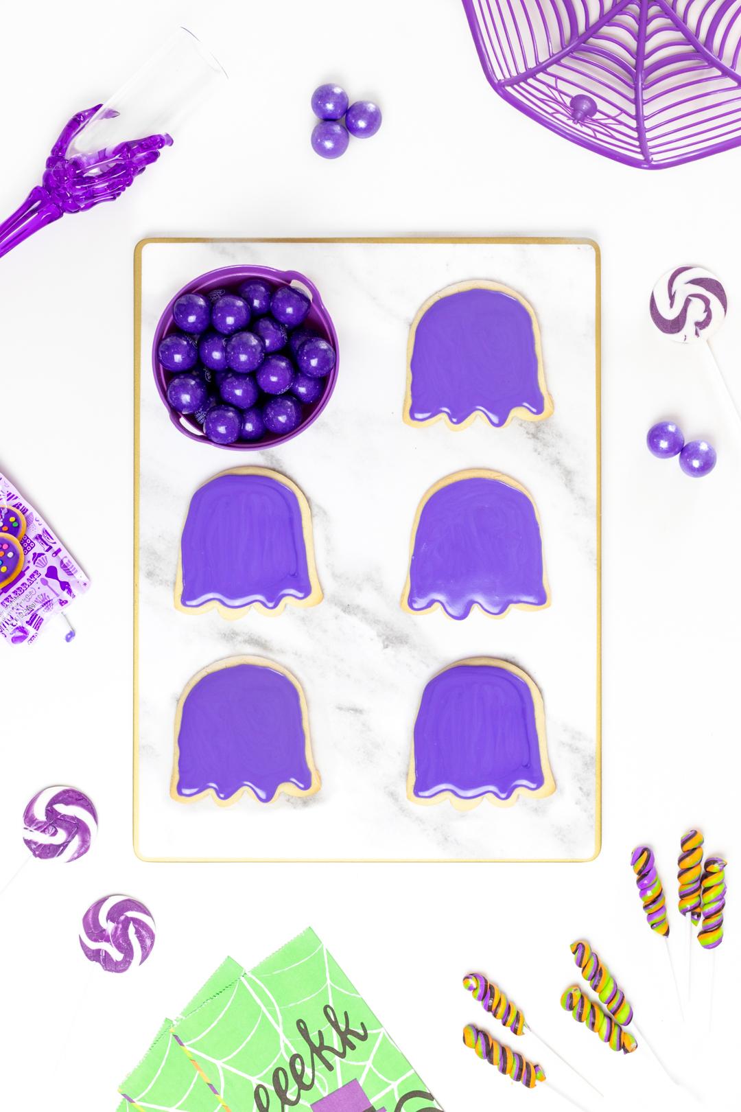 purple iced halloween cookies on a tray