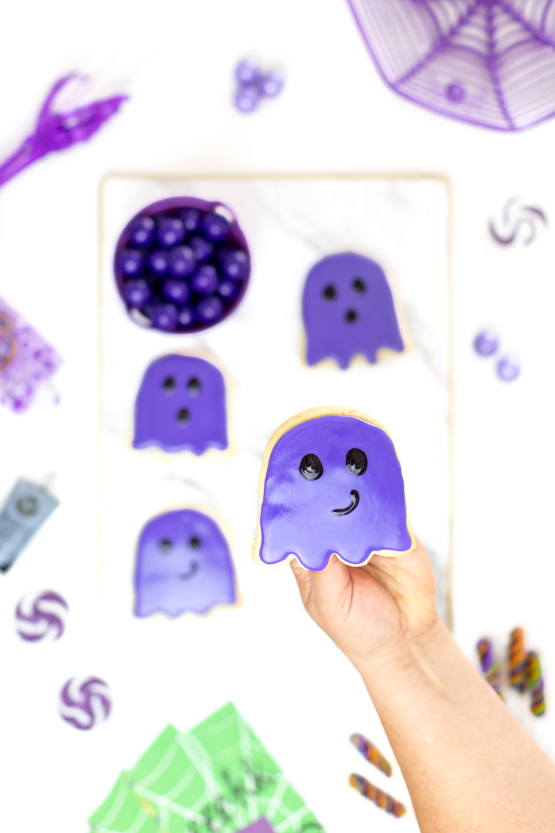 holding purple ghost cookie