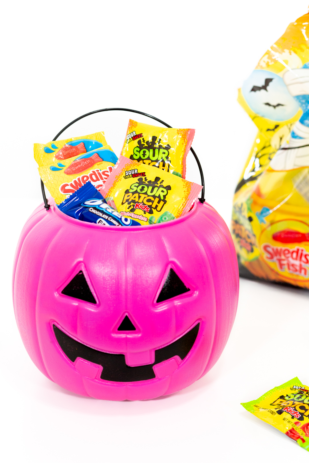 pink jack o'lantern halloween candy basket filled with swedish fish, sour patch kids and oreo candy bars