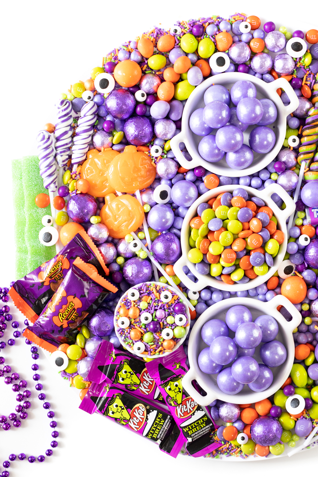 halloween candy selection. green, purple and orange. Halloween M&Ms, Gumballs, Jack o lantern Lollipops, witch chocolates