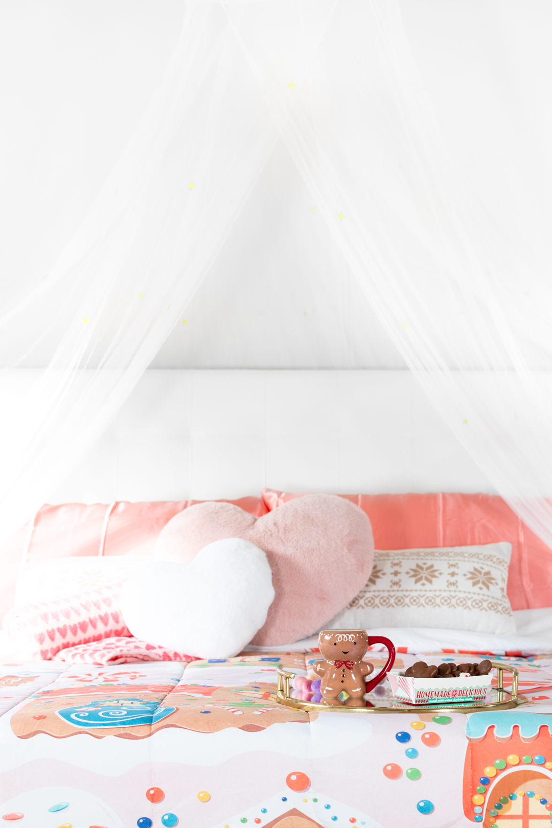 cozy christmas bedroom setup with heart-shaped pillows, gingerbread blankets and pretty tent.