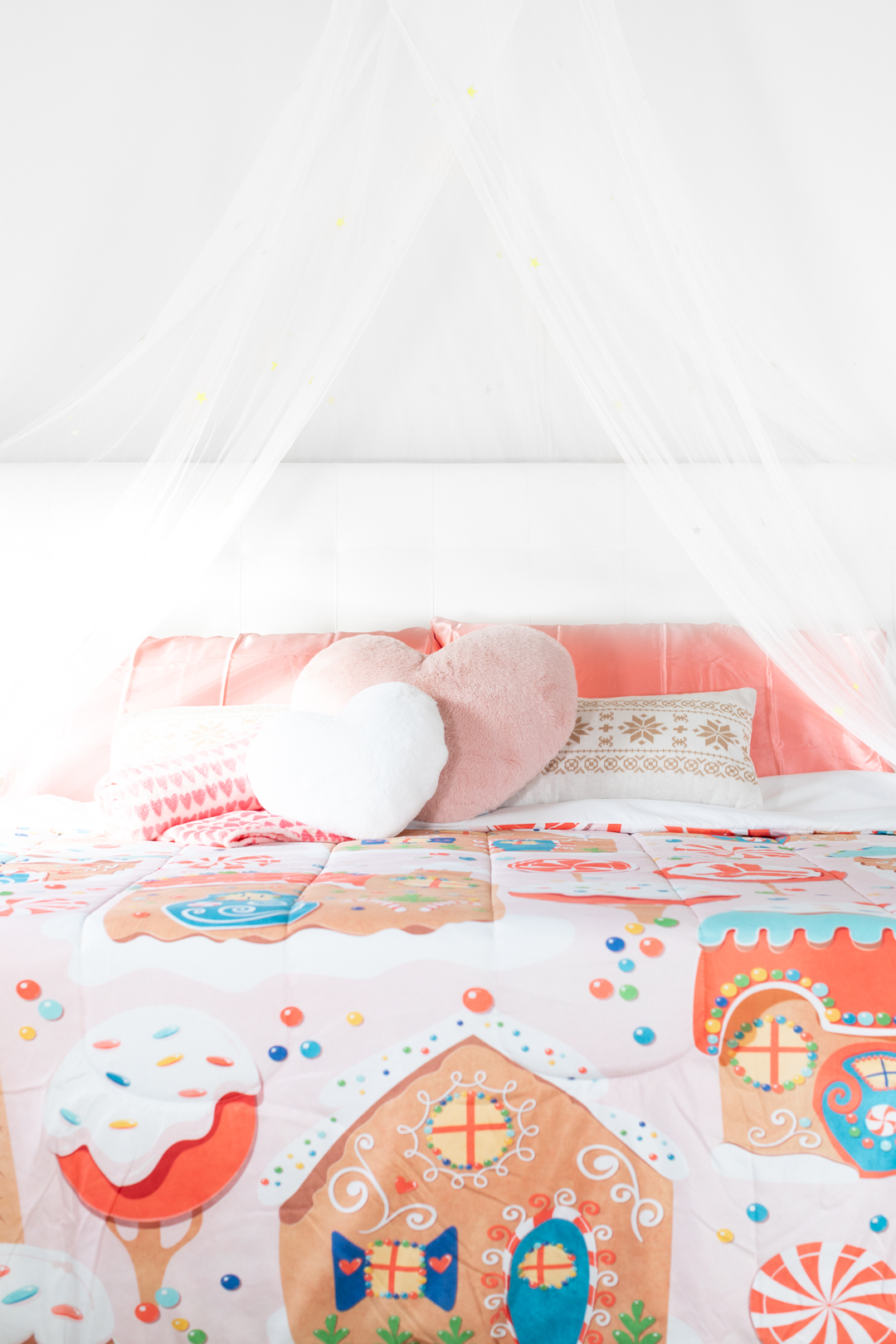 whimsical bed with gingerbread comforter, cute pillows and a sheer tent