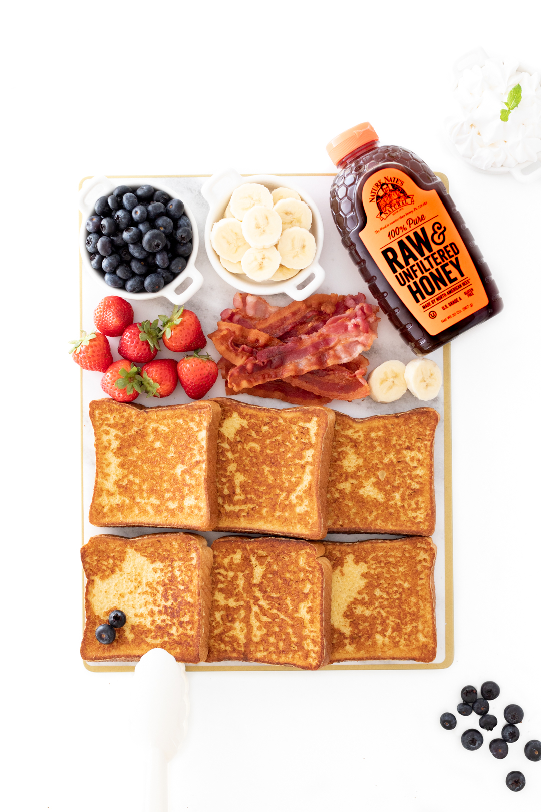 tray of french toast with fresh fruit and honey