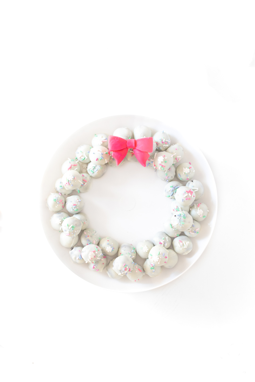 pretty OREO cookie wreath made with white OREO cookie balls and a fondant pink bow.
