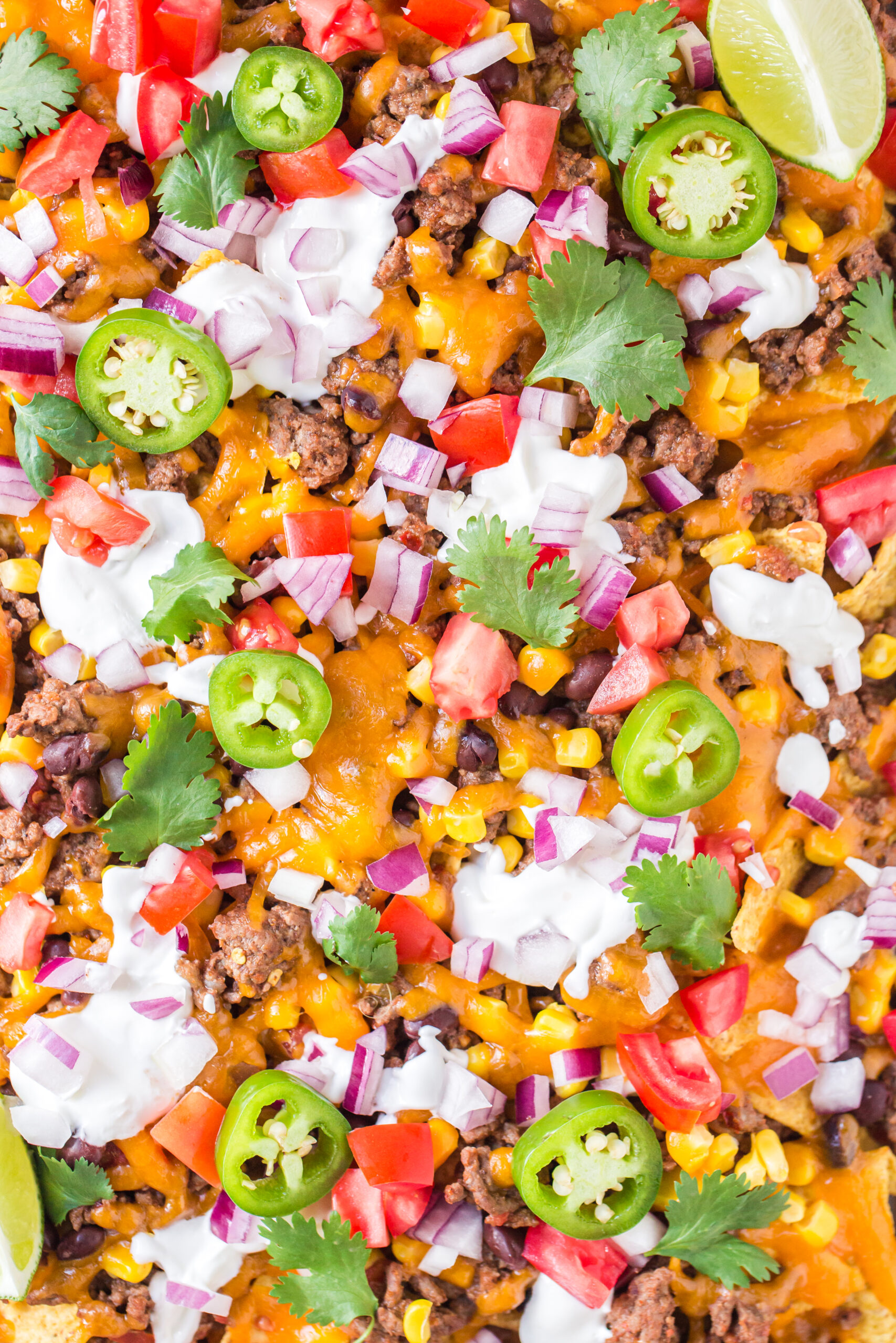 up close view of a sheet pan filled with nachos and generous toppings