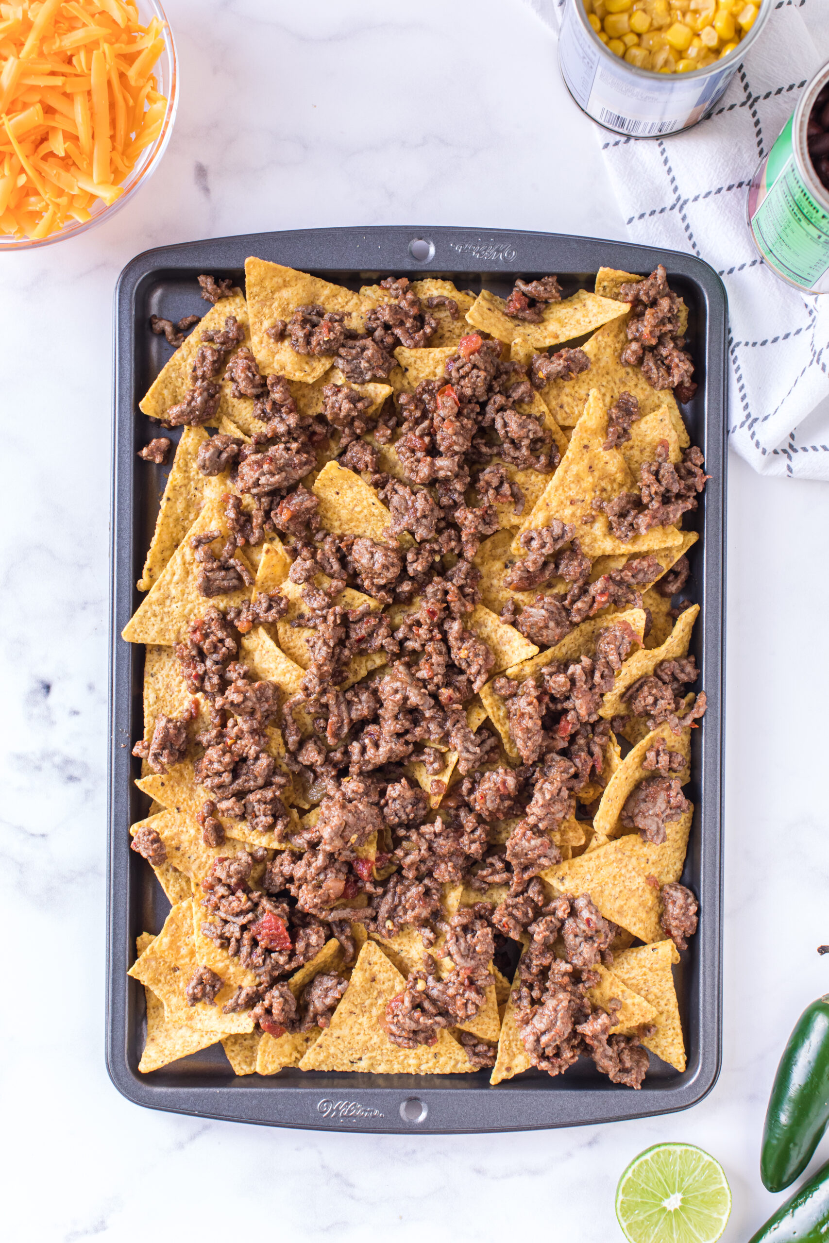 adding prepared beef to tray of nachos