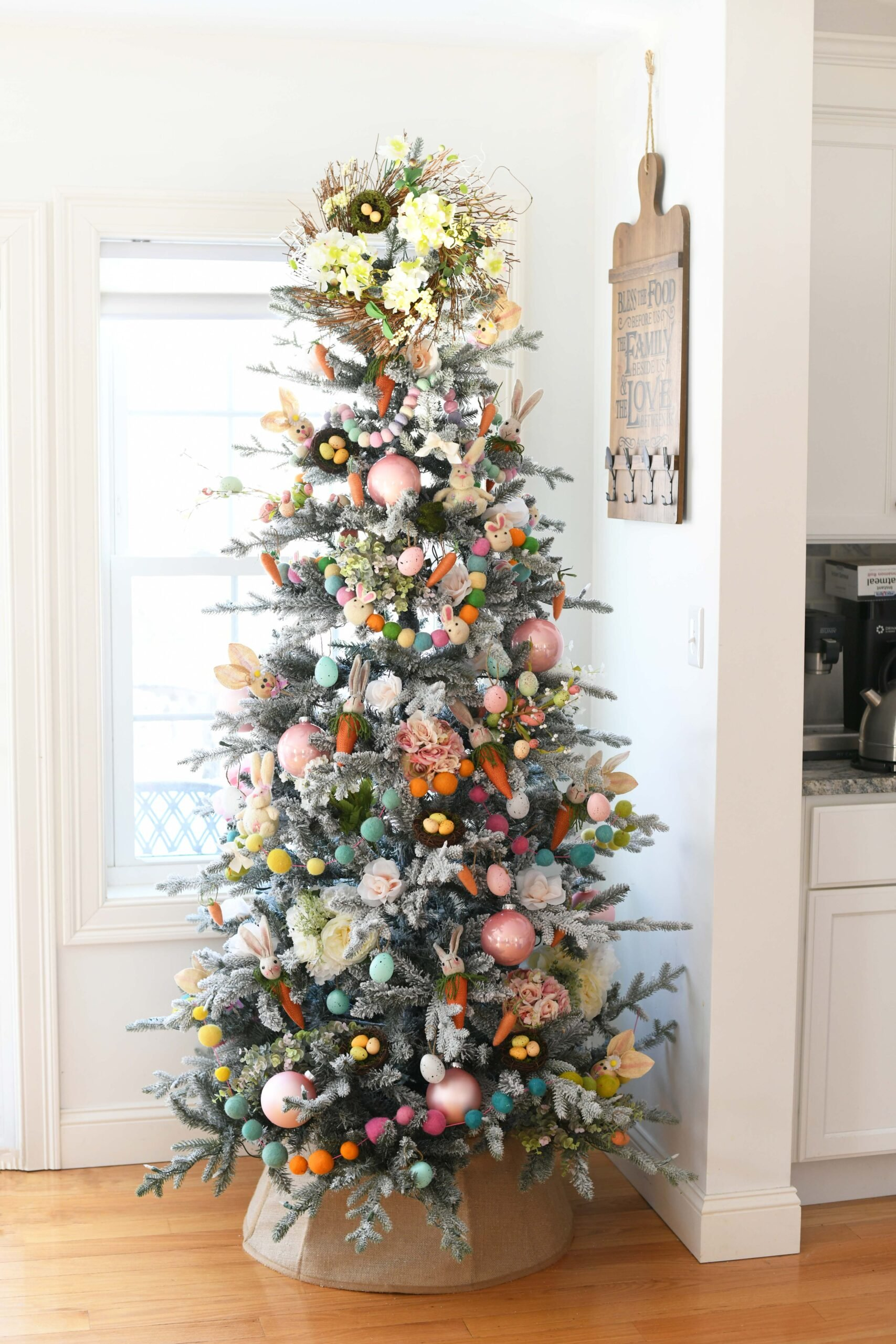 pretty farmhouse style christmas tree decorated for easter with large pom pom style garlands and pretty light easter toned decorations