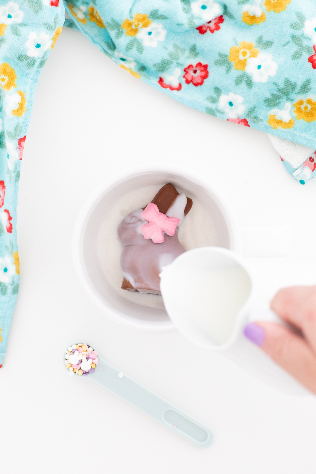 hot milk being poured over an easter bunny hot cocoa melt in a large mug