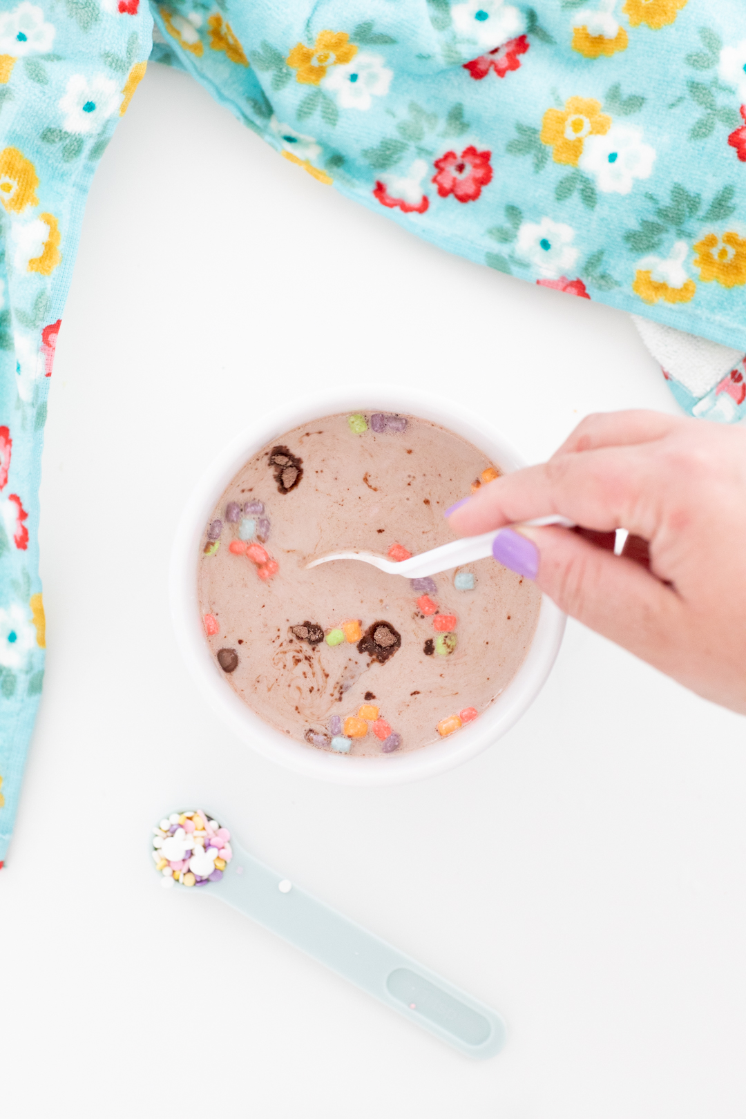 stirring an easter hot cocoa melt into a large mug. pastel mini marshmellows.