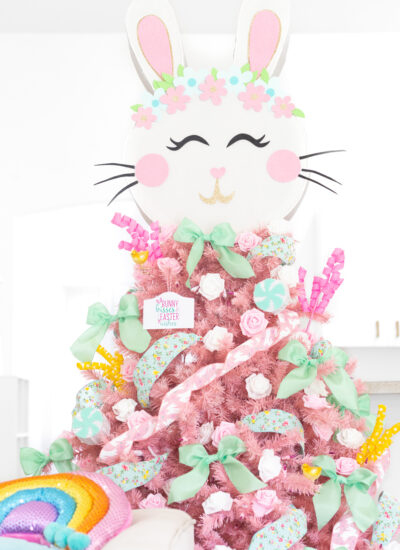 pretty pastel easter christmas tree. light pink tree with variety of pastel decorations. mint colored bows. pink and white faux flowers. Pink bunny ribbon. Large bunny pinata tree topper.