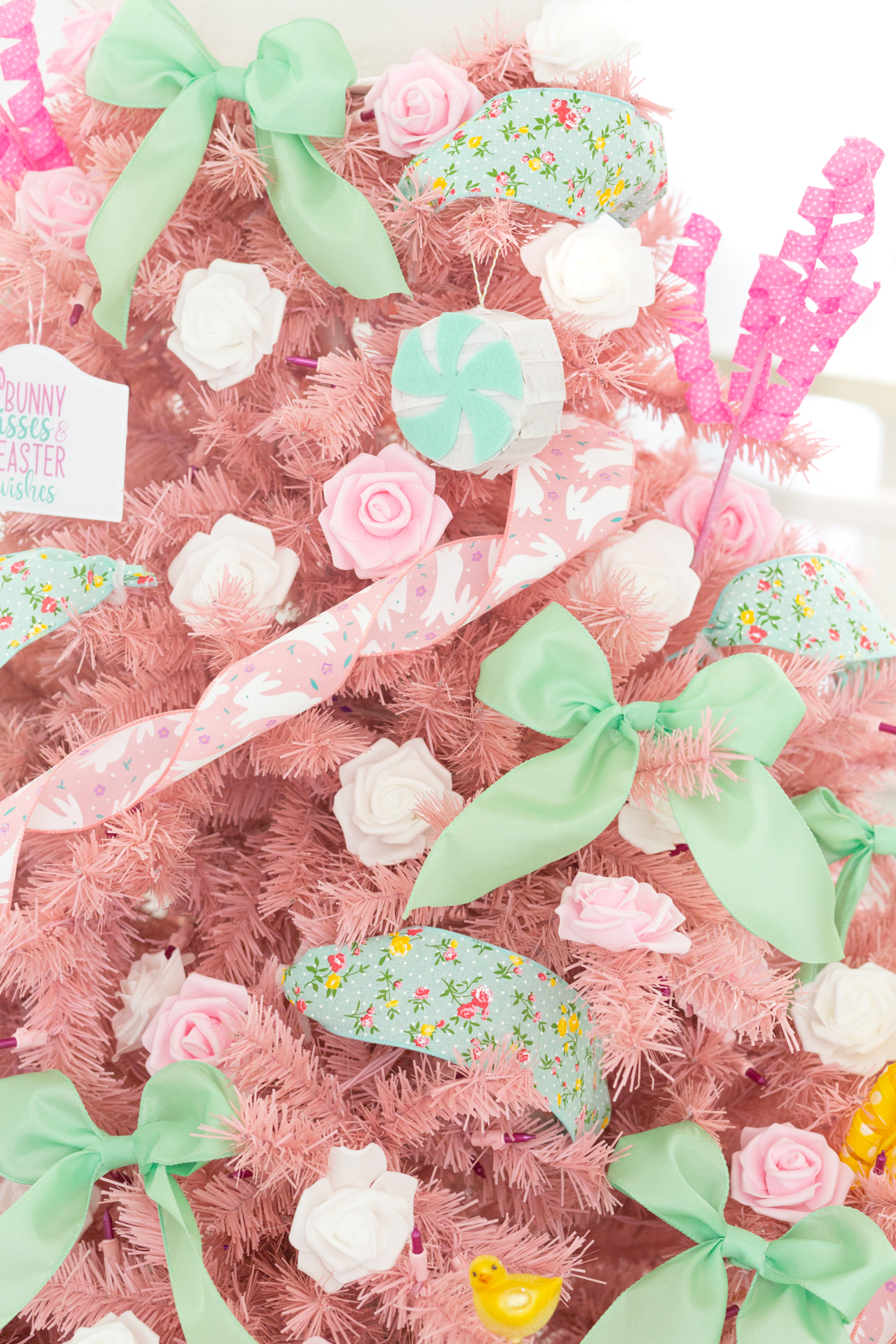 light pink christmas tree decorated for easter, up close view with decorations in focus. small flower heads, big mini ribbons, pink bunny ribbon used as garland.