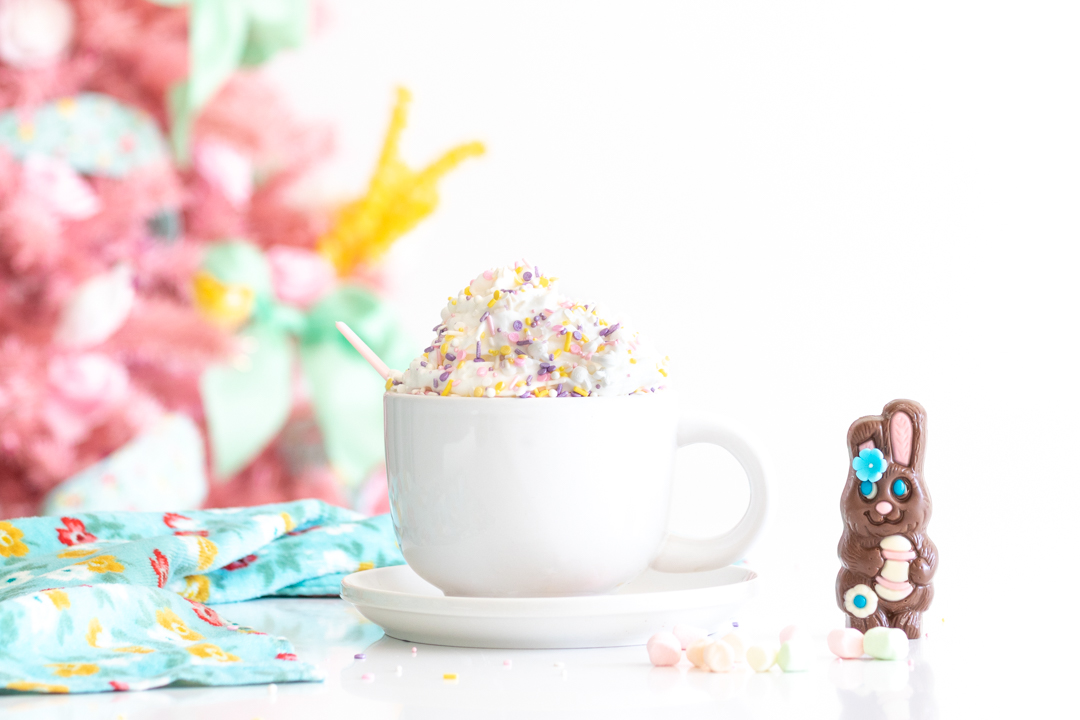 easter bunny hot cocoa melt near a mug filled with whipped cream and topped with sprinkles. pink easter christmas tree in the background with pastel decorations on it.