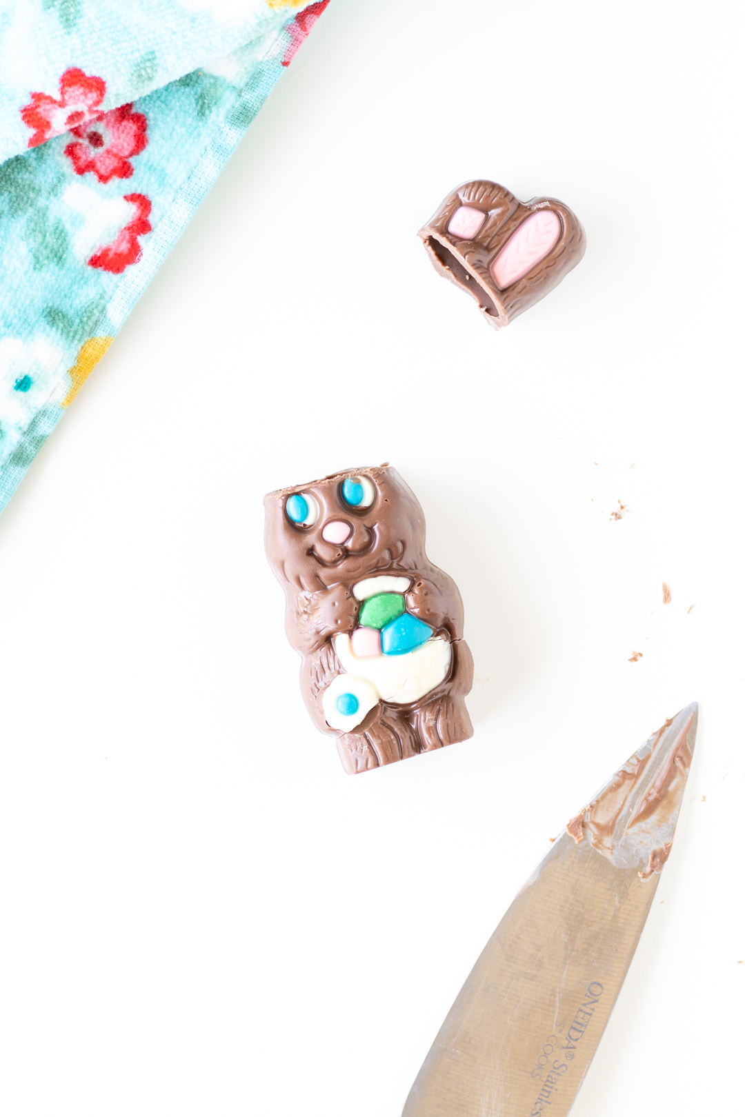 small hollow chocolate easter bunny with ears cut off. knife with melted chocolate on blade.