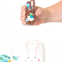 woman holding small chocolate easter bunny filled with hot cocoa mix above a mug.