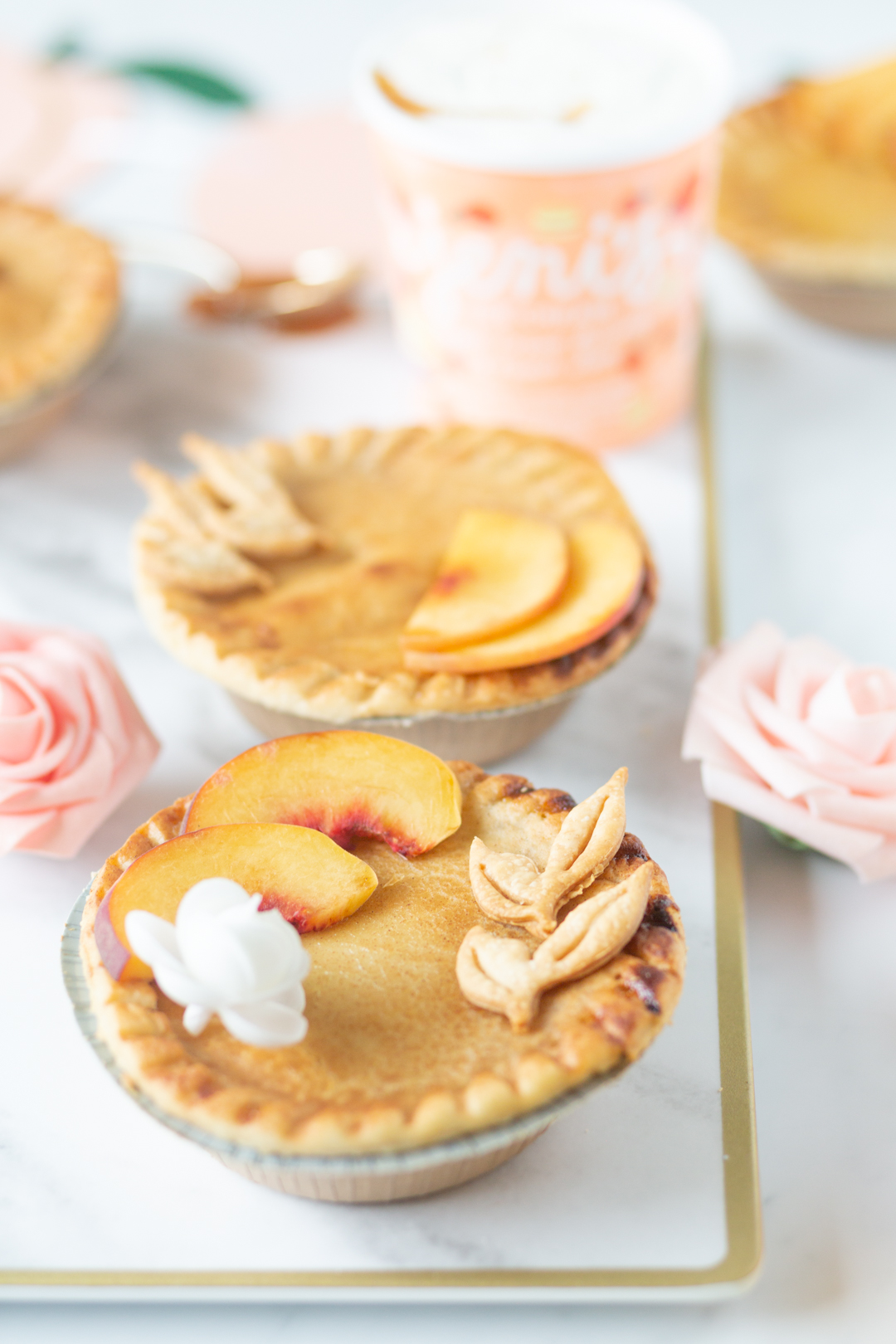mini peach pie with peach slices, edible flower and pie crust leaves on top.