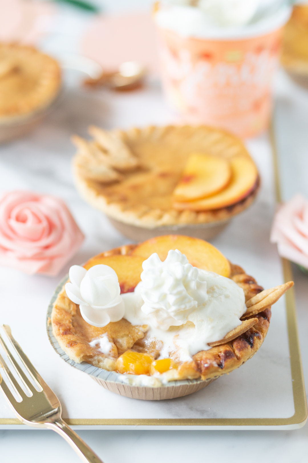 mini peach pie with ice cream and whipped cream on top.