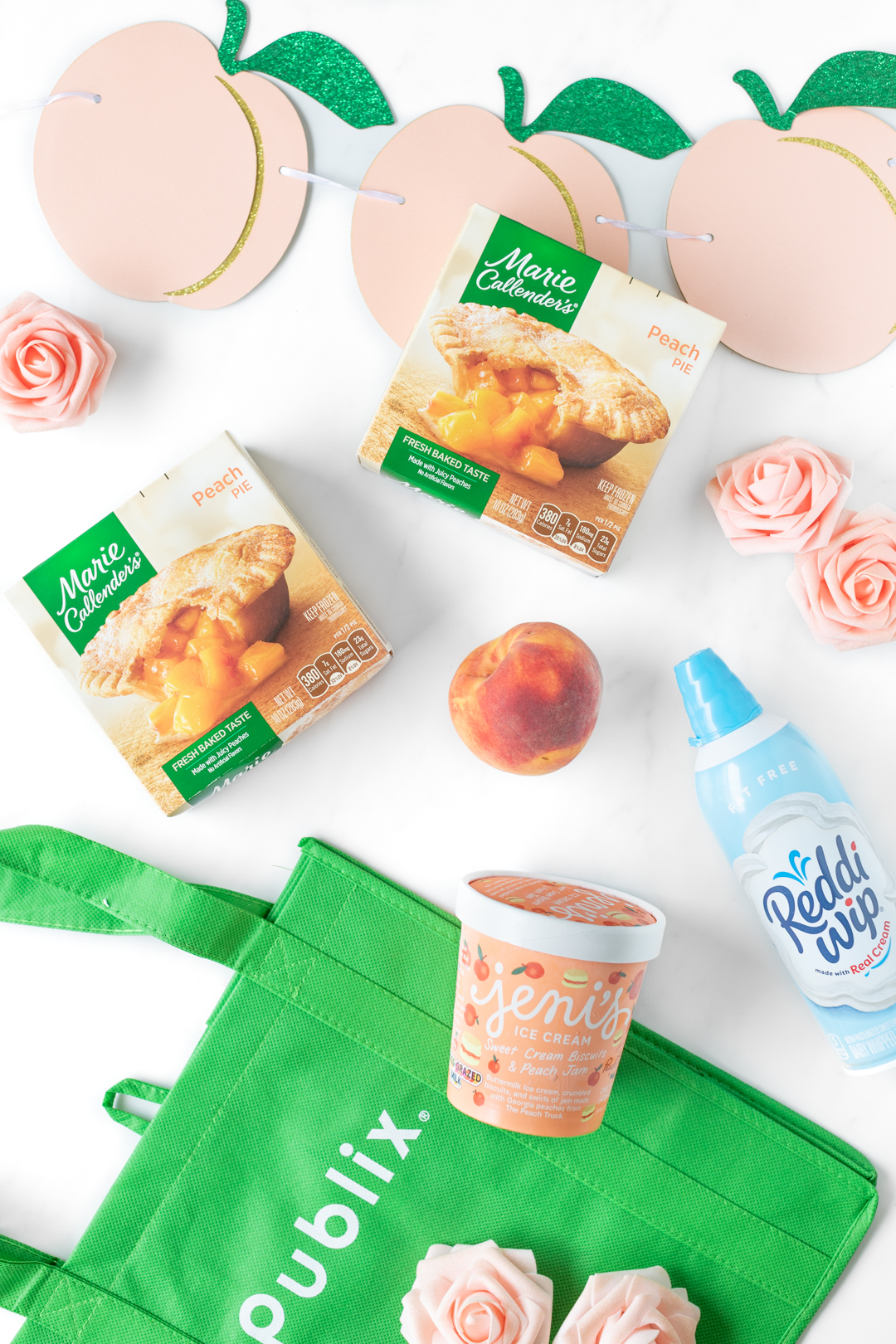 publix shopping bag with groceries including Jeni's ice cream, marie callendar's peach pies and Reddi-whip.