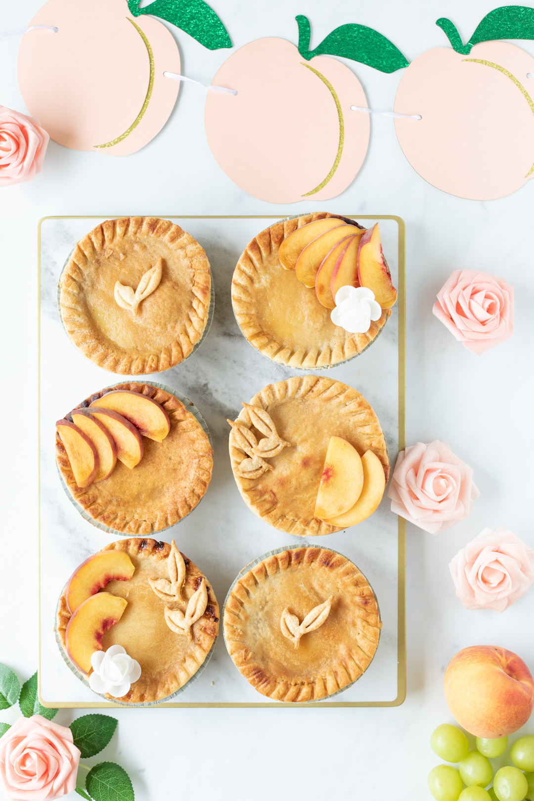 pies set out on a rectangular platter with peach colored decorations like faux flowers and peach banner.