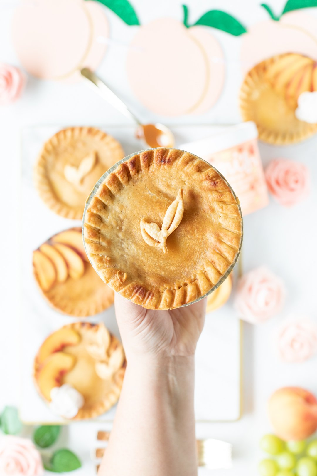 mini peach pie being held by woman's hand. Pretty leaf made out of pie crust on top.