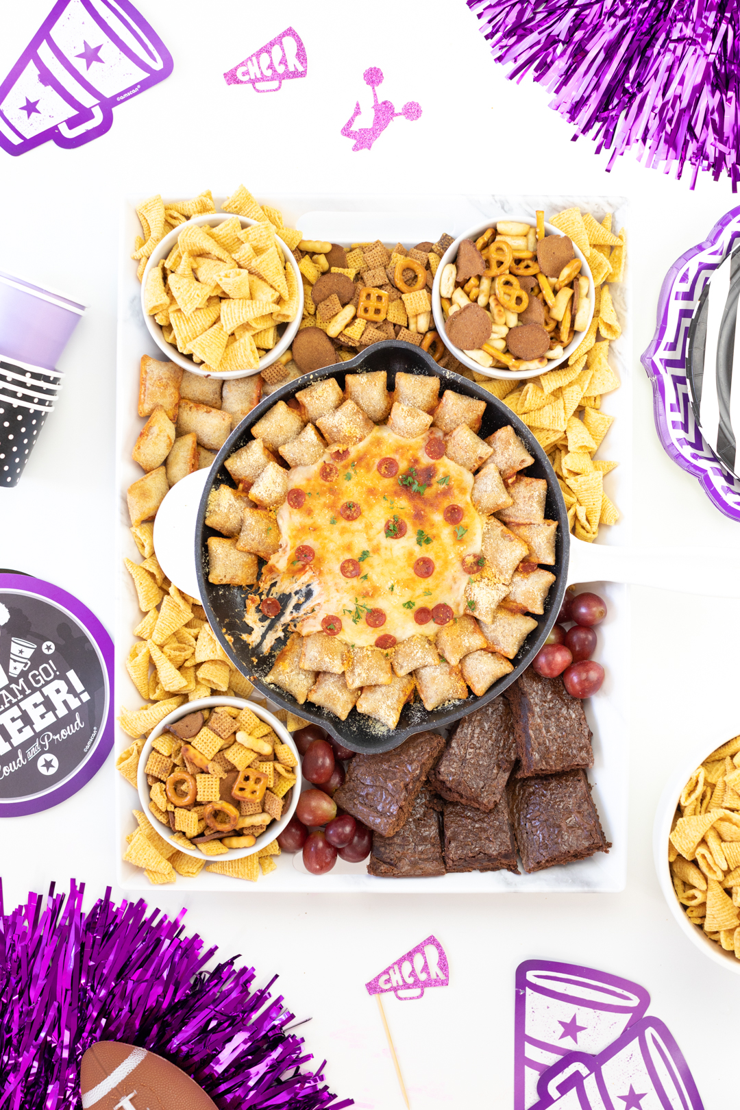 pretty tray of football snacks with pepperoni skillet dip, chex mix, bugles, brownies, grapes. Tablescape decorated with purple and black cheerleading party supplies. Alternative for football decorations.