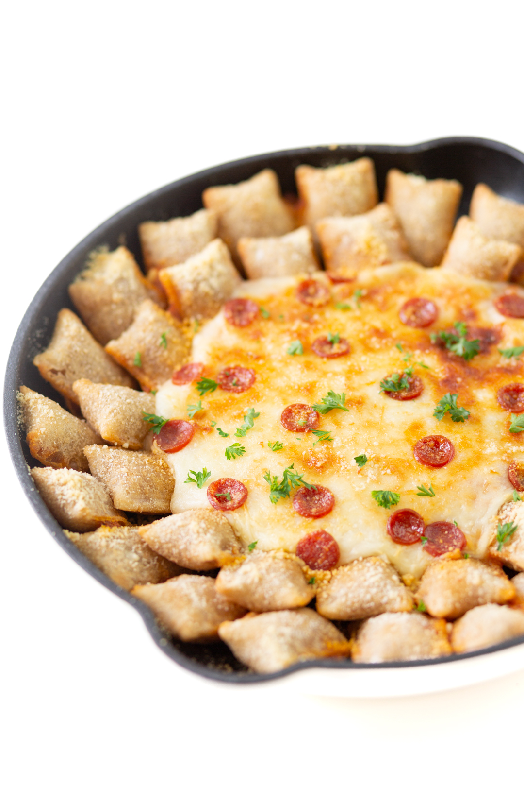 hearty dip made in a skillet with cheese, mini pepperoni and lined with pepperoni pizza rolls. Topped with snippets of parsley for garnish.