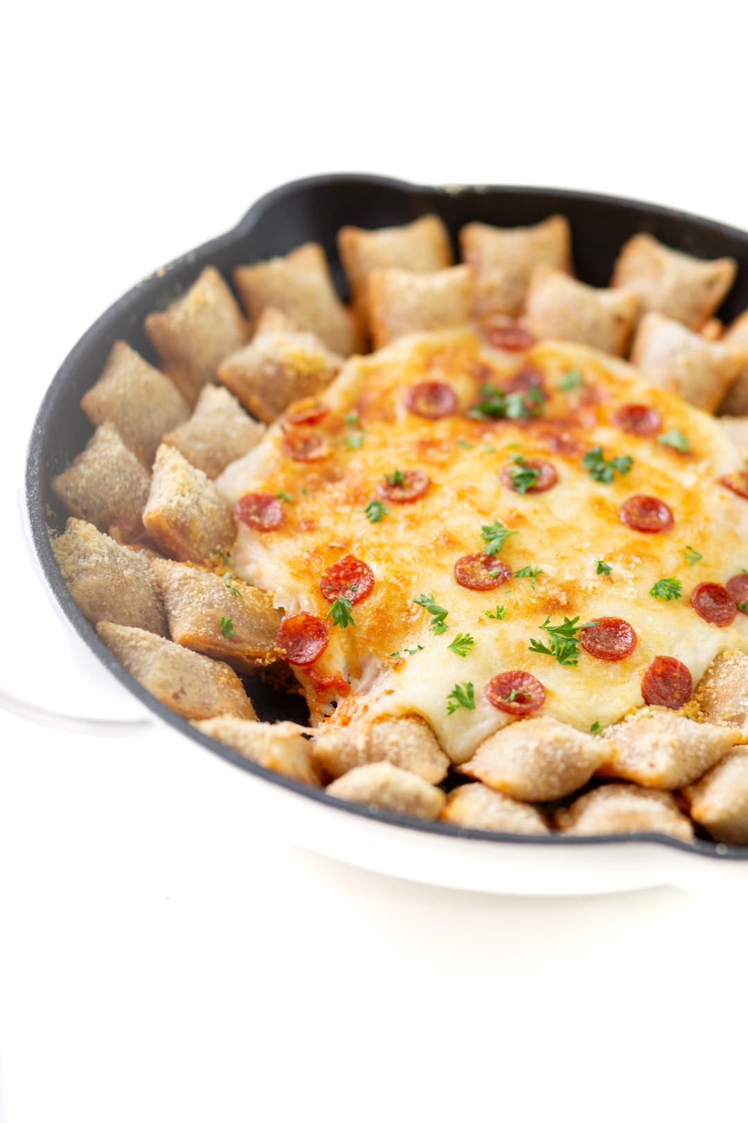 pepperoni pizza roll skillet dip with one pizza roll eaten to reveal the cheesy goodness inside the skillet