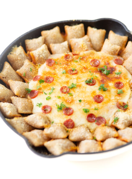 cheesy pepperoni dip up close being served in a skillet with totinos pizza rolls, melted cheese, crispy mini pepperoni and snipped parsley garnish.