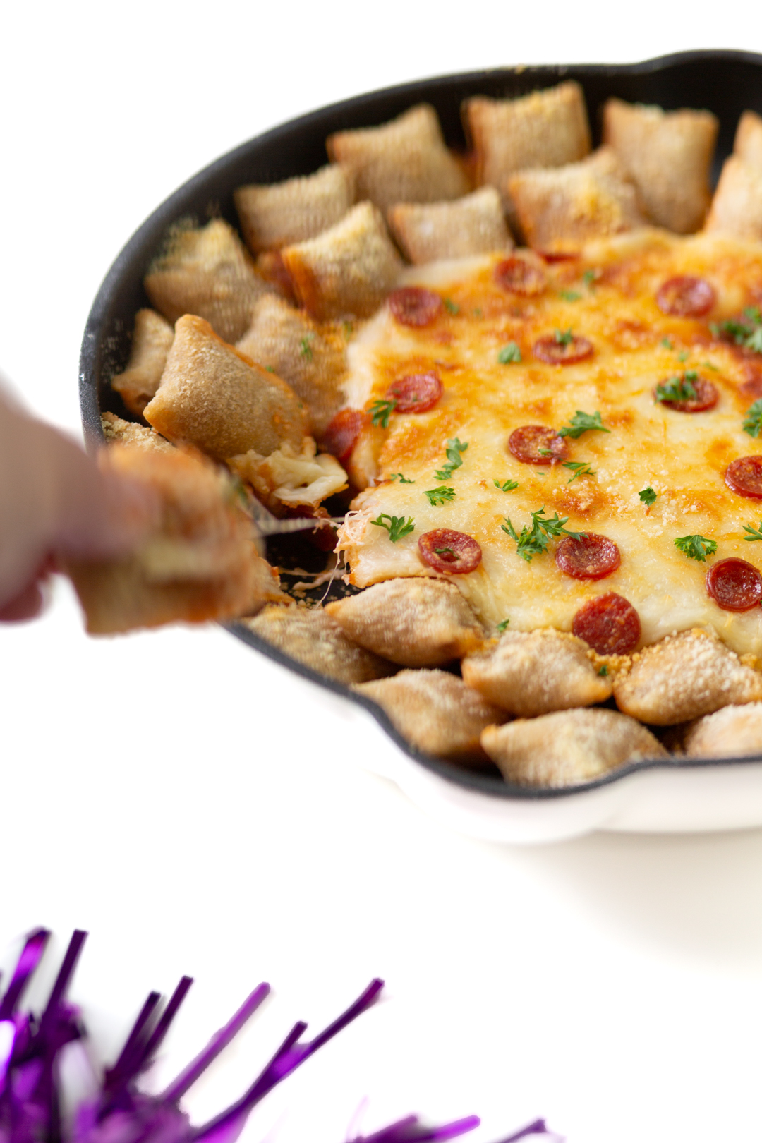 woman grabbing pizza roll from a cheesy pizza dip in a skillet