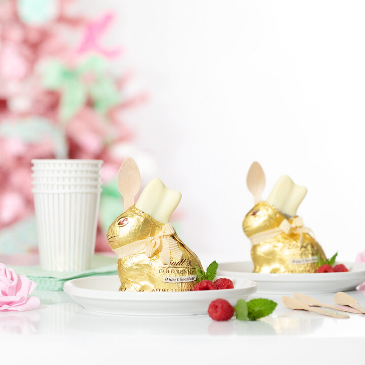 cute easter desserts. individual trifles inside of lindt white chocolate bunnies. pink easter tree in the background. pretty pink faux roses as tablescape decor