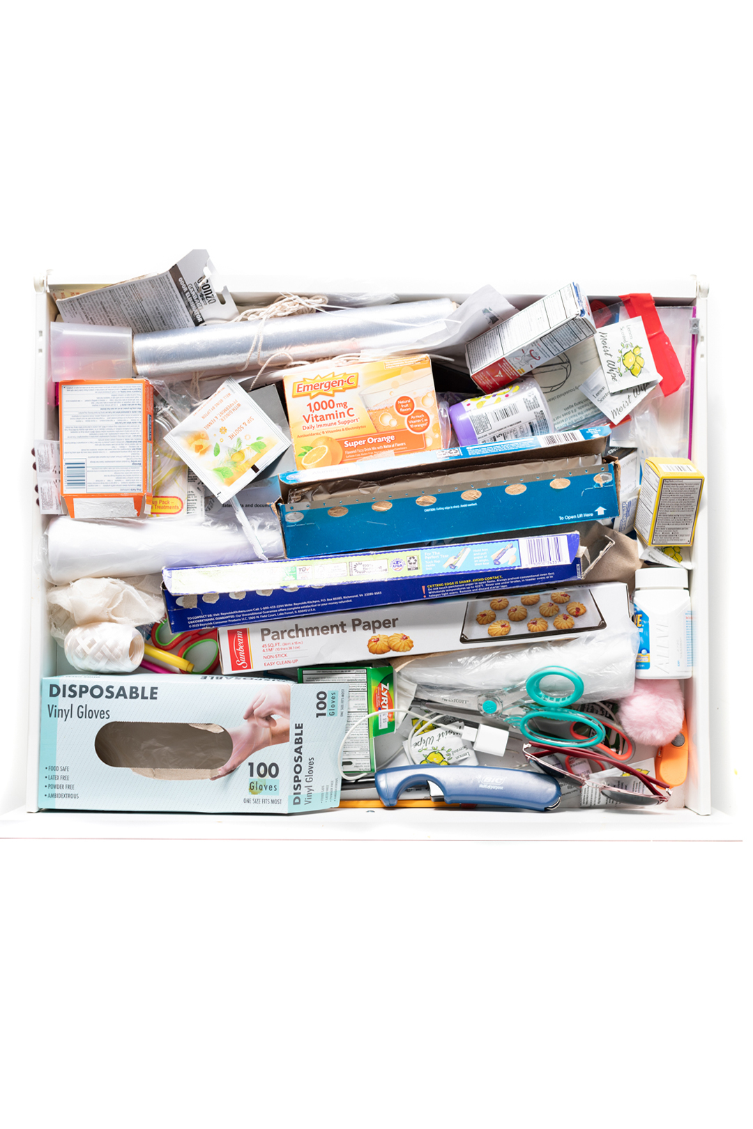 messy junk drawer with a variety of random items stuffed into from medicines to foil.