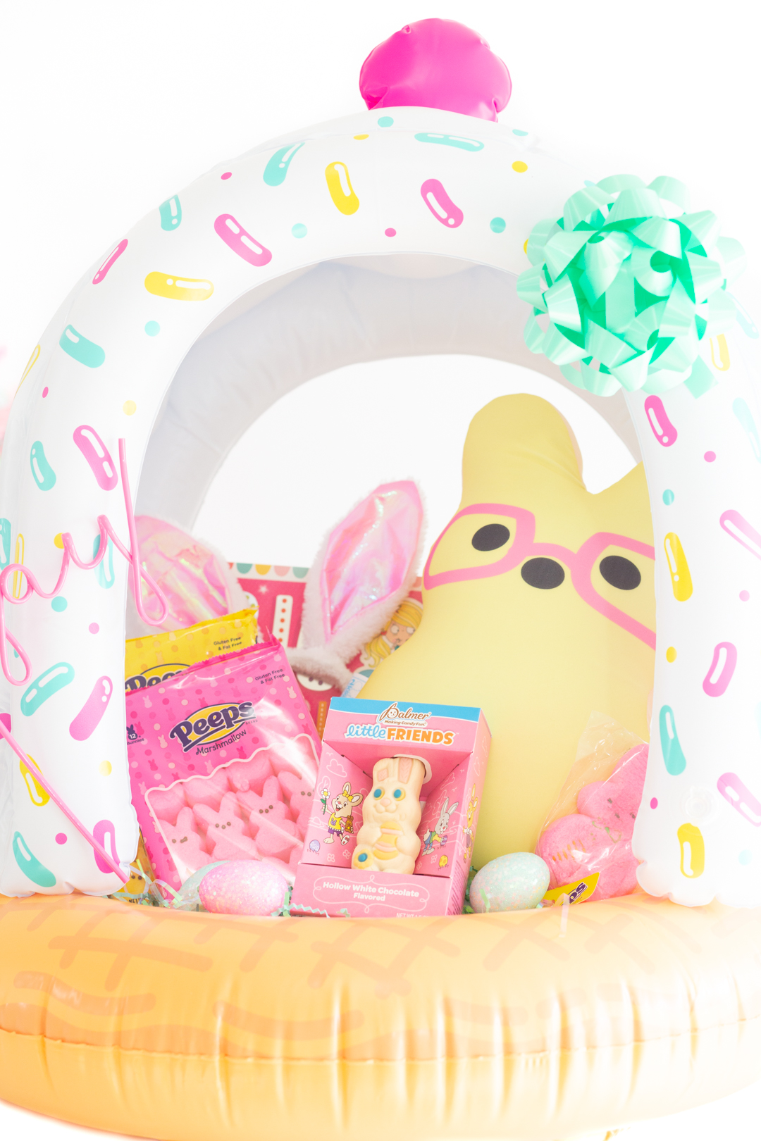up close pastel easter basket with yellow stuffed bunny with pink glasses, pink peeps and a white chocolate hollow bunny
