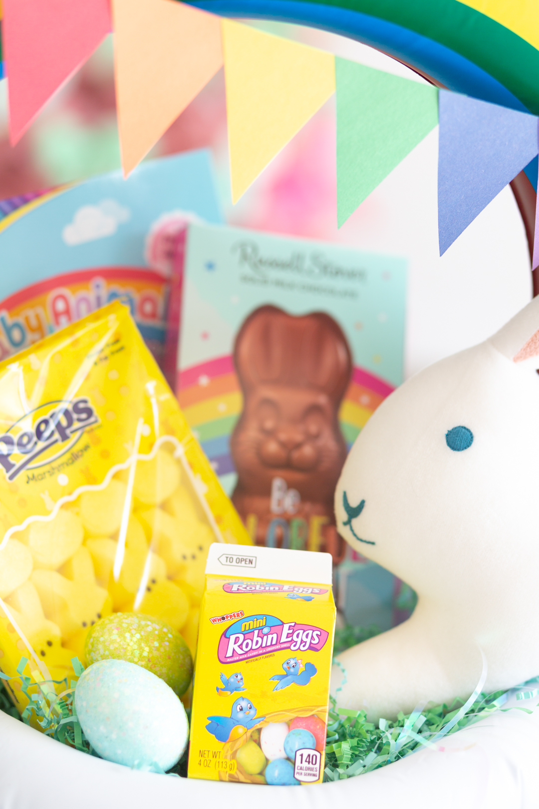 up close view of easter basket fillers including robin's eggs, yellow peeps bunnies, chocolate bunny and stuffed bunny pillow. Rainbow pendent banner made with construction paper.